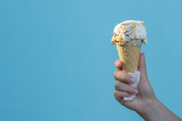 Ice cream cones in the hand of a girl on azure background