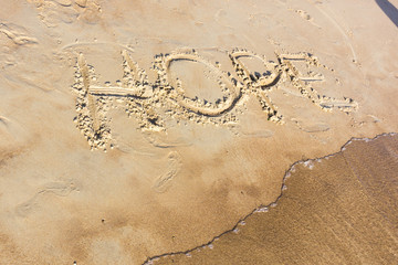 Hope written in the sand on a sunset beach