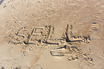 Sell written in the sand on a sunset beach
