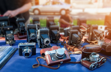 Old cameras are sold at a street market on a Sunny day.