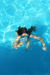 Young girl dives in the blue water of the pool