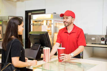Worker serving food at a concession stand