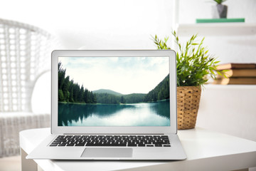 Workplace with laptop and wallpaper of landscape on screen