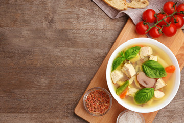 Composition with homemade turkey soup in bowl on wooden table