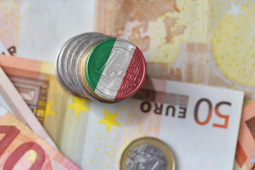 euro coin with national flag of italy on the euro money banknotes background.