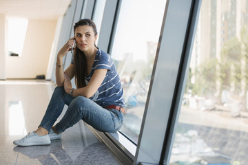 Young woman is waiting at the open space with windows