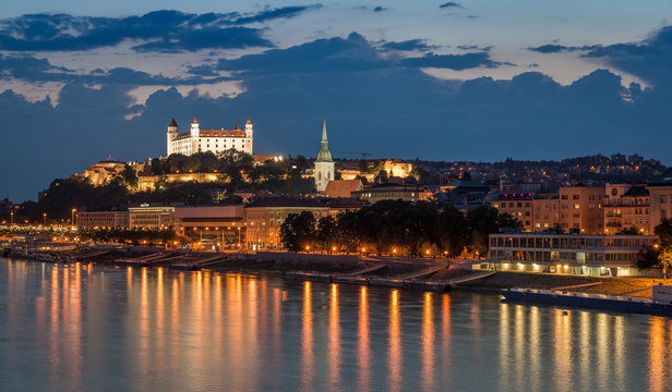 Bratislava castle at night with light reflection on the dunaj river on right riverside.