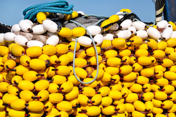 Yellow floats on the pile, covering fishing nets on the blue boat in the summer sun, close up. Fishing floats with rope knot netting piled in a fishing boat.