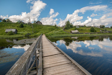 north Russian village Isady. Summer day, Emca river, old cottages on the shore, old wooden bridge and clouds reflections.
