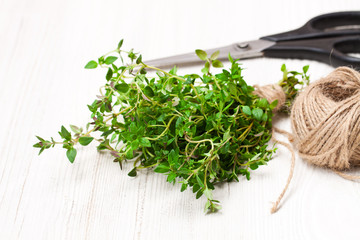 Fresh  bunch of thyme and kitchen scissors on white table