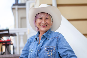Elderly woman in cowboy hat, looking at camera and smiling. On open air.