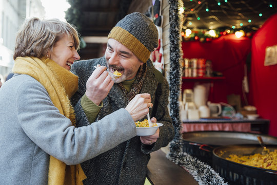 Elderly Couple Eating at Christmas Market