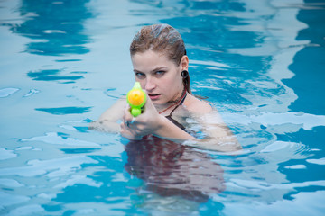 Young pretty caucasian girl with blue eyes shoots with a water gun in the pool.