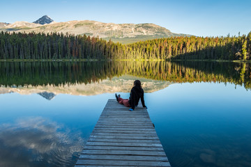 Girl Sitting on dock enjoying the mountains and morring light