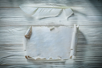 Vintage crumpled paper roll quill on wooden board
