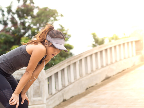 Female runner athlete resting and catching the breath after marathon training in the park at sunset, Standing bent over