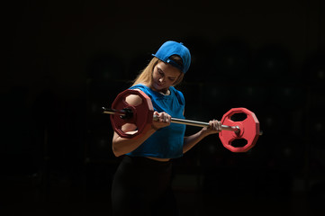Portrait of blonde female exercising with barbell