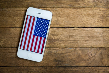 USA flag on mobile phone on wooden background for usa national day, 4th july, business, national day