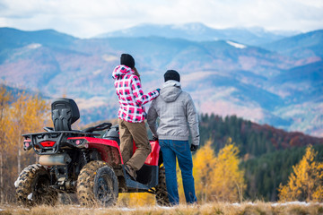 Rear view of woman standing on a red quad bike and keeps the shoulder standing next man enjoying the mountain autumn landscape