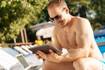 Upbeat man watching a video on tablet