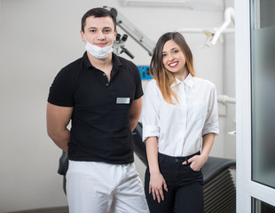 Portrait of handsome male dentist with smiling female patient after treatment in modern dental clinic. Dentistry