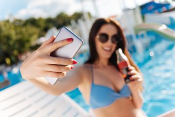 Upbeat woman taking a selfie with soda bottle