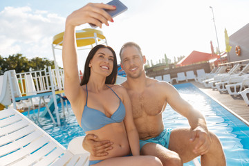 Beautiful couple taking selfie near swimming pool
