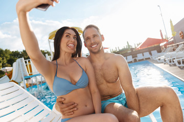Cheerful couple making funny selfies on vacation