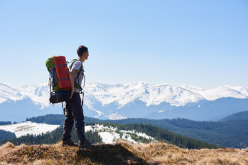 Male hiker with a backpack on his back taking in the view from the top of a mountain copyspace beauty nature landscape hiking travelling active lifestyle concept.