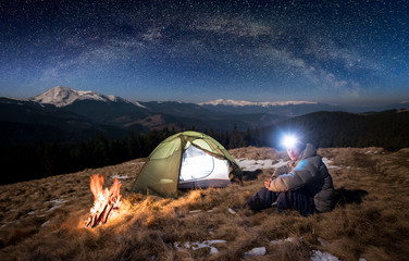 Male tourist have a rest in his camp at night. Man with lighting headlamp sitting near campfire and tent, looking to the camera under beautiful sky full of stars and milky way