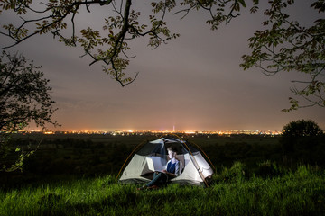 Woman using her laptop in the camping at night. Woman sitting in the tent under trees and night sky. On the background luminous city