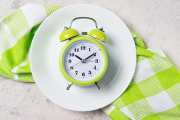 Alarm clock with bells on the plate, lunch time concept, top view with copy space