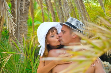 Romantic relationship in the summer.  holiday romance,  man and a woman under a palm tree. A loving couple on the island. Summer tourism. Honeymoon on a tropical island