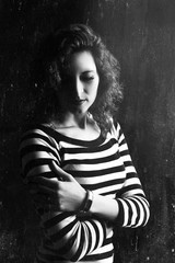 Black and white portrait of a young beautiful girl on a dark background. Photo of a woman in the style of an old photo. A dark image of a girl with a pensive, brooding look.