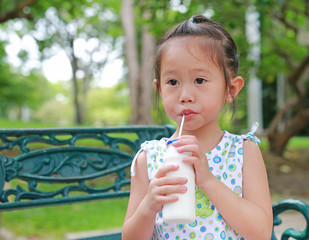 Little girl drinking milk with straw in the park.