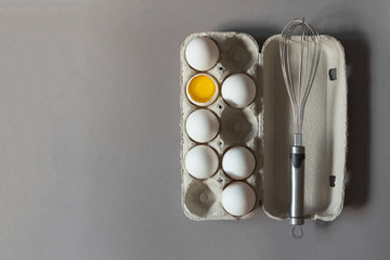 Carton of raw chicken eggs and metal whisk on gray background. Broken egg. Yolk.