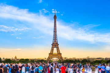Paris Tourist Place / Colorful large group of unrecognizable people blurred in front of Paris Eiffel Tower at evening light (copy space)