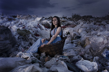 A girl in an old basket in a garbage dump