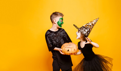 Kids Boy and Girl in Different Halloween Costumes Smiling and Frighten, Play with Pumpkin Isolated on Yellow Background.
