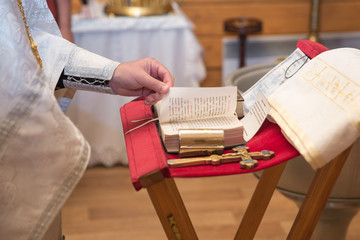church utensil on an altar, glans, cross on the church altar,the Bible on the table, ceremony of water christening