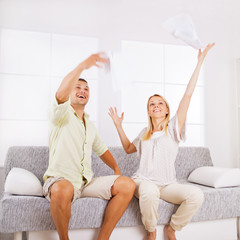 Happy mid-adult couple throwing papers in the air.