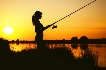 Ingelijste posters Vissen Silhouette of a woman engaged in sport fishing