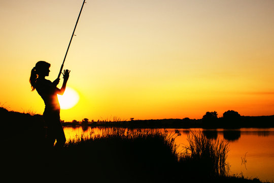 Silhouette of a fishing woman at dawn