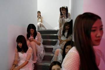 Girls rest on stairs at the China Digital Entertainment Expo and Conference (ChinaJoy) in Shanghai