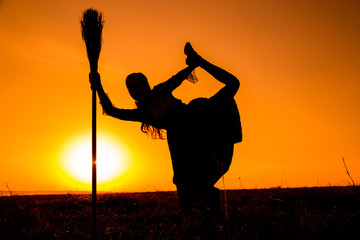 Silhouette of young witch dancing on the broomstick