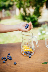 Placing Blueberries In The Glass Bottle