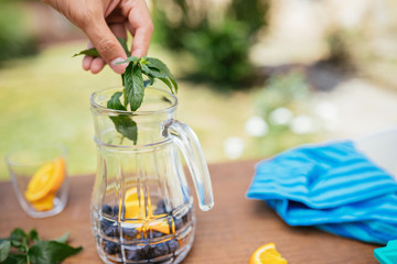 Placing Mint In The Glass Bottle With Blueberries And Orange