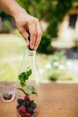 Placing Blackberry In Glass Bottle