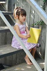 Beautiful little girl in dress reading old book and preparing for school on stairs in a yard