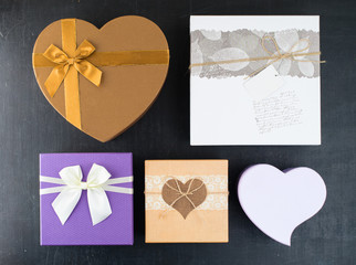 plenty assorted colorful and different in the shape and size gift boxes on dark background for the celebration of different holidays, flat lay